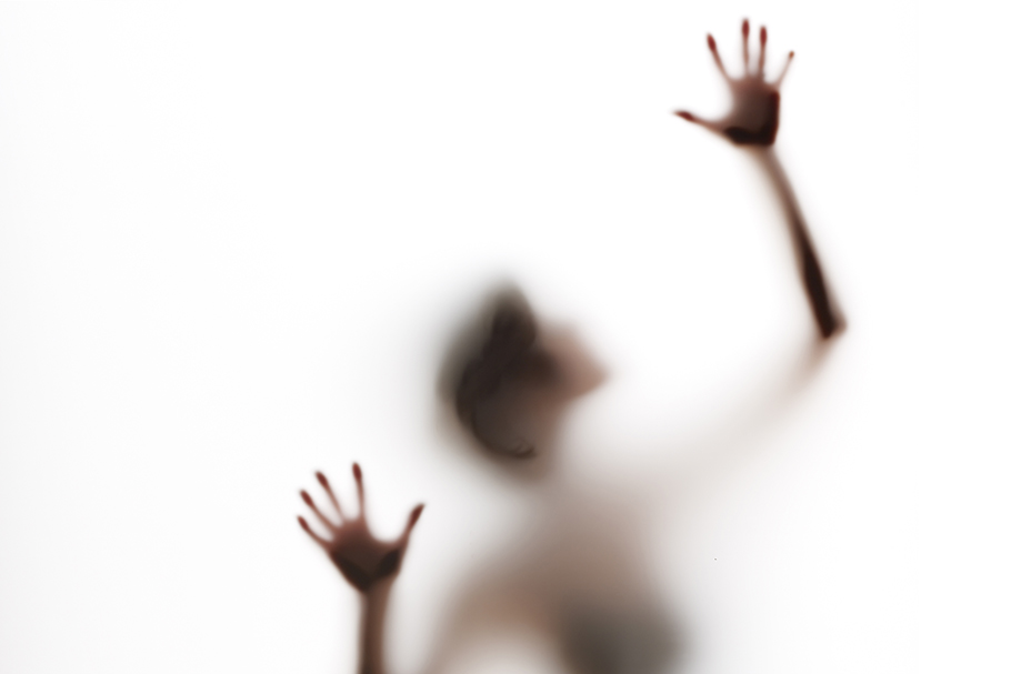 semi-obscured figure with arms raised