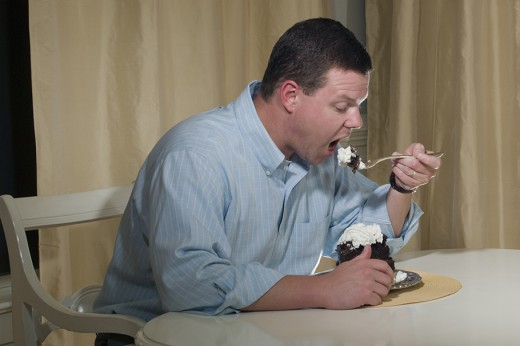 Mid adult man sitting at table, eating chocolate cake