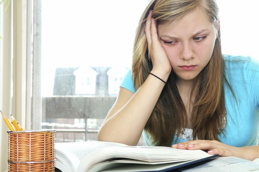 Teenage girl struggling with textbooks