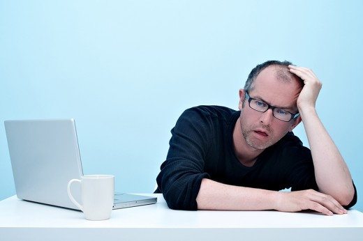 Man at desk leaning his head on his hand